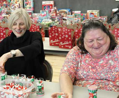 Mary Flynn, left, daughter of Christmas Stocking founder Katheryn Etter, packs candy for senior cheer boxes with Monda Hess